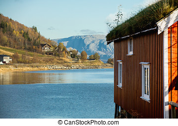 Red wooden house on stilts with a grass roof. Mountains in...