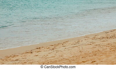 Waves crashing gently on quiet sandy beach. Full HD stock...