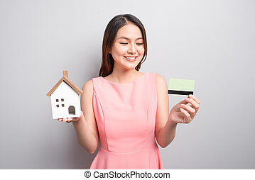 Invest in real estate concept. Woman holding small toy house and credit card in hands