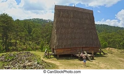 Flycam Shows Traditional Wooden House with High Narrow Roof...