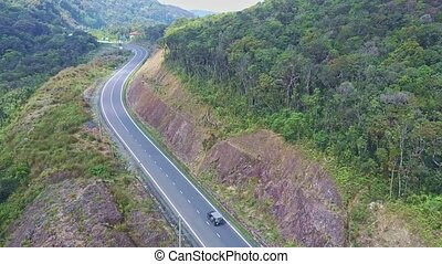 Flying Camera Moves over Mountain Road after Driving Car
