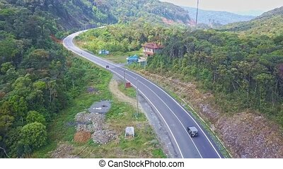 Flying Camera Shows Car Driving along Mountain Road and Motel