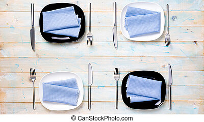 perfect table setting with black and white plates for four