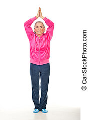Aged woman doing yoga - Smiling aged woman in pink sport...