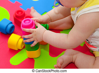 Toddler plays with building block on the colored rubber mat.