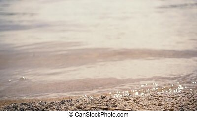 Slow mo. Waves on a sandy beach. Sand in focus, water...