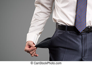 Concept of bankruptcy. Businessman turns out an empty pocket.