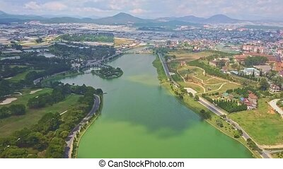 Flycam Moves over Beautiful Quiet Lake against Modern City -...
