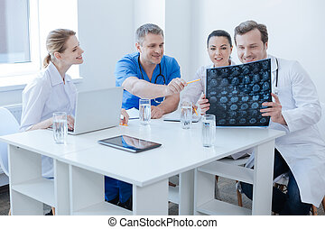 Optimistic radiologists discussing brain x ray image at the...