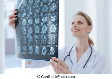 Cheerful medical specialist examining x ray at the...