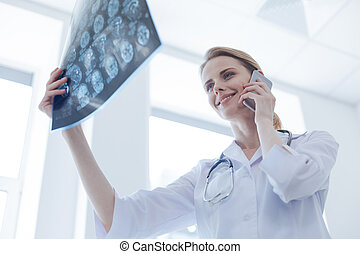 Glad radiologist analyzing brain x ray at the laboratory -...