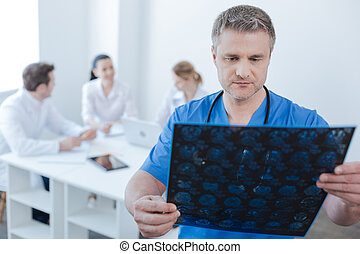 Serious neurologist examining mrt scan photo at the...