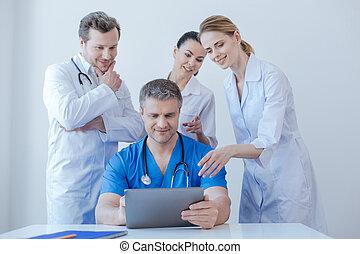 Delighted medics enjoying new digital gadget at work -...