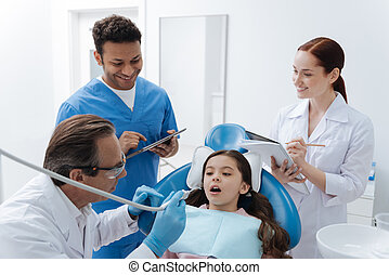 Scared girl looking at her dentist