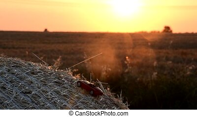 Car model moves on a round bale at sunset