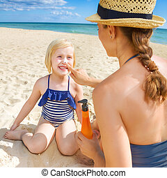 happy young mother and daughter on seashore applying SPF -...