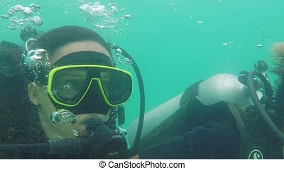 Young woman diving her first time with oxygen cylinder in...