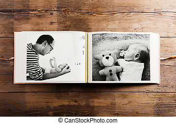 Photo album with pictures of father and baby son. Fathers...