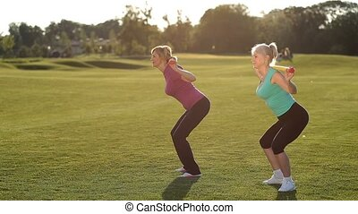 Slim adult women doing squats with bodybar in park - Side...