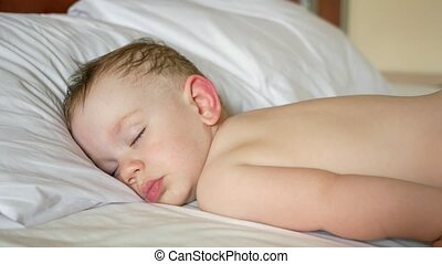 Boy is sleeping on a white bed without a shirt. A little...