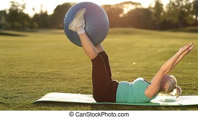 Adult woman making exercise with fitball in park - Side view...