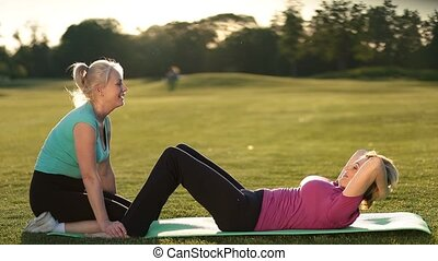 Lady doing abdominal crunches exercise on mat - Side view of...