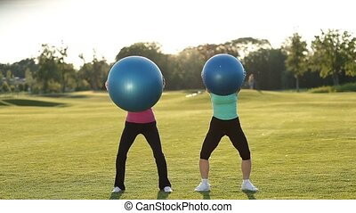 Fitness ladies squatting with fitball outdoors - Beautiful...