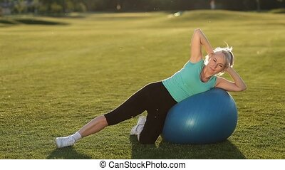 Sporty fit lady doing side crunches on ball - Beautiful...