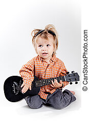 Cute little boy playing ukulele guitar, studio shot