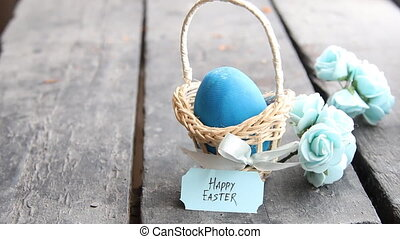 Happy easter. Blue egg on rustic table and a basket with a tag