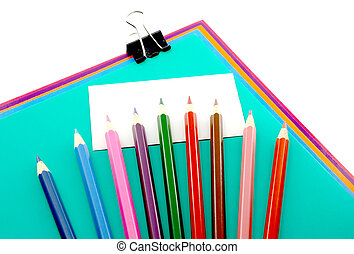 Color papers, black clip and color pencils over white label