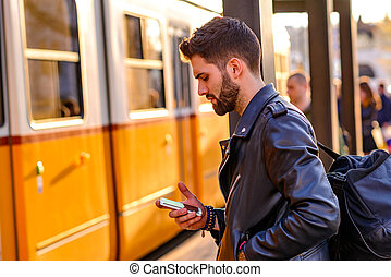 Young man waiting in a tram station