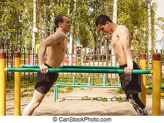 Fitness men at the bar. Exercising outdoors in the Park....