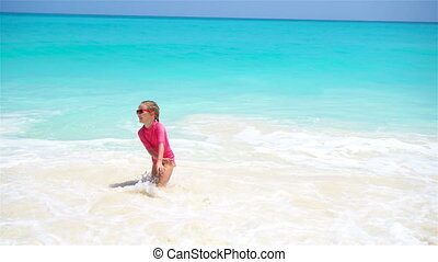 Adorable little girl at beach having a lot of fun in water -...