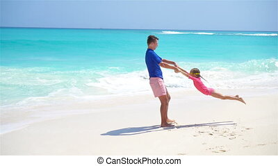 Little girl and happy dad having fun during beach vacation -...