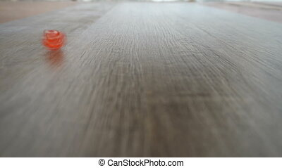 a red cube spinning on grey laminate.