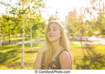 Summer girl portrait. Happy woman smiling on sunny summer or spring day outside in park. Pretty Caucasian woman outdoors