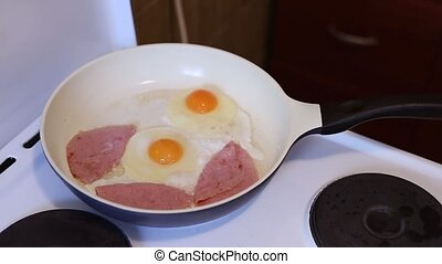Fried eggs in a frying pan fried eggs with sausage.