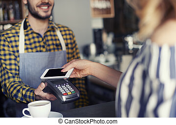 Female customer paying with credit card for cup of coffee