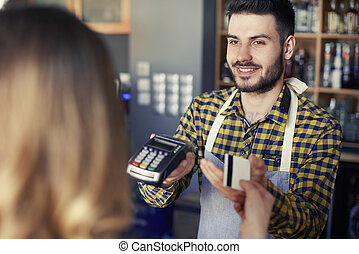 Customer paying with credit card in the coffee