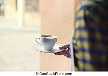 Low angle view of bartender carrying coffee