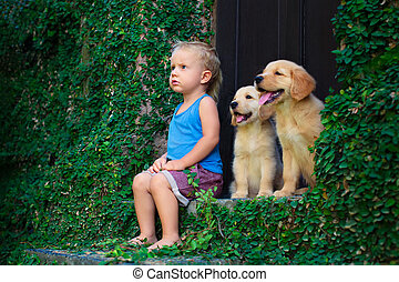 Happy baby boy sitting with two golden labrador retriever...