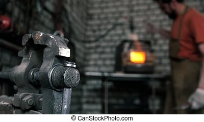 In the forge. Vise on the background a blurry furnace - In...
