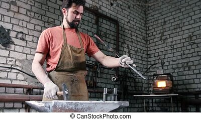 The blacksmith holds in his hands the tongs with the knife blanks