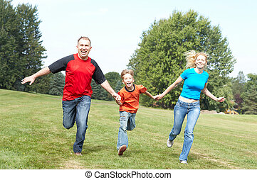 Happy family Father, mother and sons running in the park