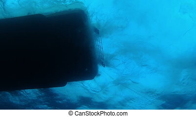 Underwater view of the hull of a dive boat with working...