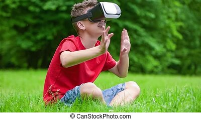 Teen boy with VR glasses in park - Playful teen boy using...