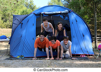 Smiling family with three happy children and tent in camping