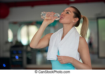 Middle-aged woman athlete drinking bottled water