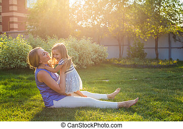 happy harmonious family outdoors. mother laughing and playing with baby daughter girl in the summer on the nature